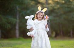 Mała Kaukaska dziewczyna w świątecznej sukni z pluszowym biel zabawki królikiem, patrzejący kamera, ono uśmiecha się fotografia royalty free