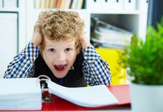 Mała Kaukaska kędzierzawa chłopiec chwytał jego głowę podczas gdy siedzący Fotografia Royalty Free