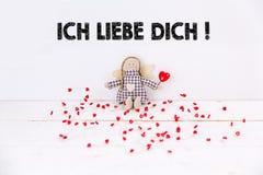 Mała kukła siedzi na białym tle z z czerwonymi sercami «Ich liebe dich «tekstem Tranlation: «kocham ciebie « zdjęcia stock
