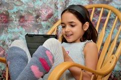 Mała Latynoska dziewczyna Cieszy się jej nową pastylkę obrazy stock