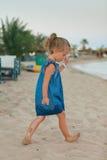 Mała młoda dziewczyna bawić się na dennym wybrzeżu Obrazy Royalty Free