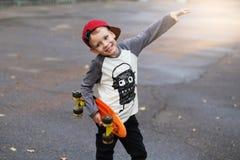 Mała miastowa chłopiec z centu deskorolka Dzieciak jazda w th Obraz Stock