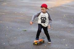 Mała miastowa chłopiec z centu deskorolka Dzieciak jazda w th Zdjęcie Stock