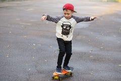 Mała miastowa chłopiec z centu deskorolka Dzieciak jazda w th Fotografia Royalty Free
