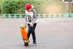 Mała miastowa chłopiec z centu deskorolka Dzieciak jazda w th Zdjęcia Stock