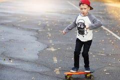 Mała miastowa chłopiec z centu deskorolka Dzieciak jazda w th Obrazy Royalty Free