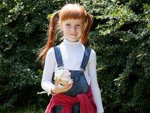 Mała miedzianowłosa dziewczyna w niebieskich dżinsach z piegami Zdjęcia Royalty Free