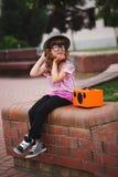 Mała modniś dziewczyna słucha muzykę na bezprzewodowym retro przyglądającym spea Fotografia Royalty Free