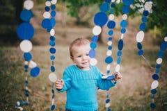 Mała mody chłopiec jest ubranym błękitnego jeanse i pulower w lesie Zdjęcia Royalty Free