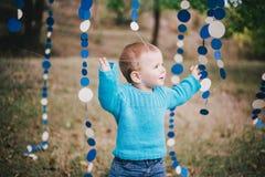 Mała mody chłopiec jest ubranym błękitnego jeanse i pulower w lesie Zdjęcie Stock