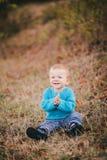 Mała mody chłopiec jest ubranym błękitnego jeanse i pulower w lesie Fotografia Stock