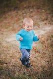 Mała mody chłopiec jest ubranym błękitnego jeanse i pulower w lesie Zdjęcia Stock