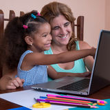 Mała multiracial dziewczyna i jej macierzysty działanie na laptopu comput Zdjęcie Stock