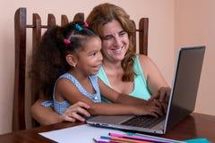 Mała multiracial dziewczyna i jej macierzysty działanie na laptopu comput Obrazy Royalty Free
