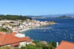 Mała nabrzeżna wioska w zatoce z plażą i wyspie z lasowym molem i łodziami, słoneczny dzień, niebieskie niebo Galicia, Hiszpania fotografia stock