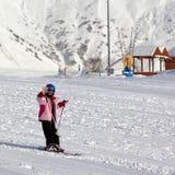 Mała narciarka przy ośrodkiem narciarskim w słońce zimy dniu Obrazy Stock