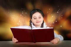 Mała nastoletnia dziewczyna czyta magiczny czarodziejski tutorial książki ono uśmiecha się Fotografia Royalty Free