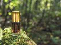 Mała nieotwarta butelka z zawartość na zielonym naturalnym tle Mała butelka agarwood olej przy naturalnym zielonym backgroun Obrazy Royalty Free