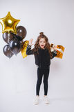 Mała nowożytna modniś dziewczyna w mod ubraniach stoi blisko balonów i chwyta złota teraźniejszości Pozy twarz Urodziny Zdjęcia Stock