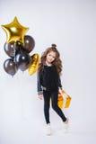 Mała nowożytna modniś dziewczyna w mod ubraniach stoi blisko balonów i chwyta złota teraźniejszości Urodziny Zdjęcie Royalty Free