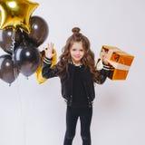 Mała nowożytna modniś dziewczyna w mod ubraniach stoi blisko balonów i chwyta złota teraźniejszości Urodziny Zdjęcia Royalty Free