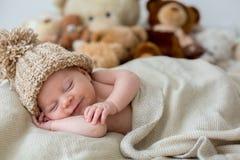Mała nowonarodzona chłopiec, śpi z misiem w łóżku w domu Zdjęcie Stock