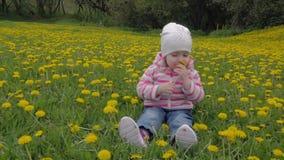 Mała, piękna dziewczyna, bawić się w parku na trawie Kwiaty, dandelions swobodny ruch zbiory wideo