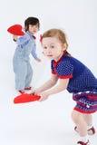 Mała piękna dziewczyna i chłopiec stoimy czerwonych serca i trzymamy Zdjęcie Stock