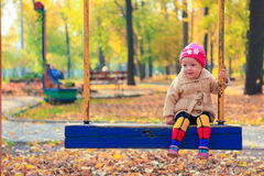 Mała piękna dziewczyna ma zabawę na huśtawce w Fotografia Stock