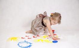 Mała piękna dziewczyna rysuje farby, ręki w farbie Obrazy Stock