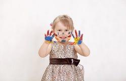 Mała piękna dziewczyna rysuje farby, ręki w farbie Fotografia Stock