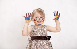 Mała piękna dziewczyna rysuje farby, ręki w farbie Zdjęcie Stock