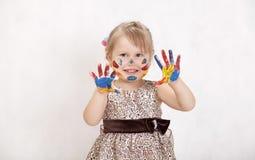 Mała piękna dziewczyna rysuje farby, ręki w farbie Zdjęcie Royalty Free
