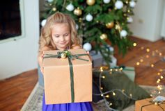 Mała piękna dziewczyna z blond kędzierzawym włosy rozciąga Bożenarodzeniowego prezent przeciw tłu choinka fotografia royalty free
