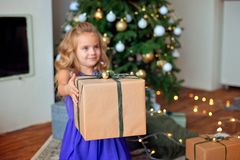 Mała piękna dziewczyna z blond kędzierzawym włosy rozciąga Bożenarodzeniowego prezent przeciw tłu choinka obrazy stock