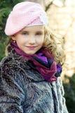 Mała piękna dziewczyna z niebieskimi oczami w różowej kapeluszowej pozyci na ulicie zdjęcia royalty free
