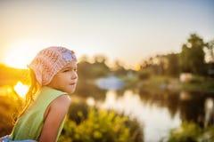 Mała piękna zadumana dziewczyna blisko jeziora przy zmierzchem Zdjęcia Stock