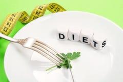 Mała porcja jedzenie na dużym talerzu w górę Mały zielony pietruszka liść na bielu talerzu z rozwidlenia, noża i teksta dietą na zdjęcia stock