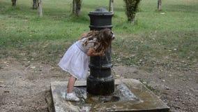Mała powabna dziewczynka w smokingowej wodzie pitnej od Romańskiej fontanny na gorącym letnim dniu zdjęcie wideo