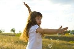Mała pozytywna dziewczyna łapie mydlanych bąble Fotografia Stock