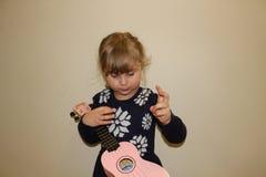 Mała preschool dziewczyna która uczy się bawić się ukulele zdjęcie royalty free