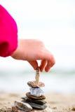 Mała ręka umieszcza kamień na ostrosłupie na piasku Morze w bac Zdjęcie Stock