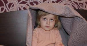Mała rozochocona dziewczyna chuje pod koc i oglądać TV Poj?cie dzieciaka sen zdjęcie wideo