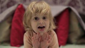 Mała rozochocona dziewczyna ma zabawę na łóżku Pojęcie dzieciaki w domu zbiory wideo