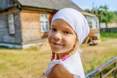 Mała spokojna dziewczyna w białym szaliku przeciw pobliskiemu wiejskiemu domowi fotografia royalty free