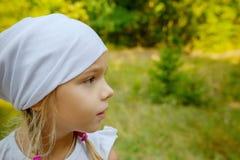 Mała spokojna dziewczyna w białym szaliku w profilu zdjęcia stock