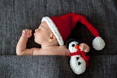 Mała sypialna nowonarodzona chłopiec, jest ubranym Santa kapelusz i trzymać zdjęcia royalty free