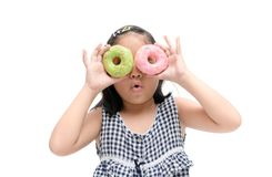 Mała szczęśliwa śliczna dziewczyna je pączek odizolowywającego Zdjęcia Royalty Free