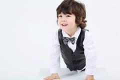 Mała szczęśliwa chłopiec opierająca się na wielkim sześcianie i spojrzeniach na boku Fotografia Royalty Free