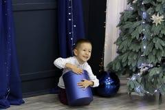 Mała szczęśliwa chłopiec siedzi na podłodze blisko choinki i otwiera pięknego prezent fotografia royalty free